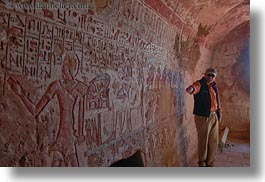 africa, ahmed, al kab, arts, bas reliefs, baseball cap, clothes, egypt, hats, horizontal, hyroglyphics, interpreting, language, people, sculptures, tombs, tour guides, photograph