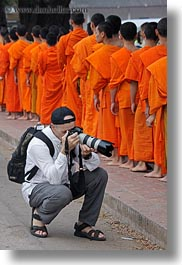asia, asian, cameras, colors, laos, luang prabang, men, monks, oranges, people, photographing, procession, vertical, photograph