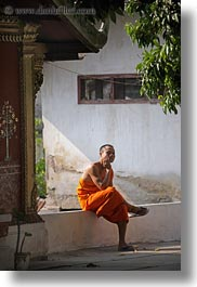 asia, asian, colors, laos, luang prabang, men, monks, oranges, people, shades, singles, sitting, vertical, photograph