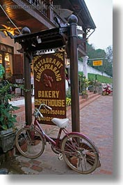 asia, bakery, bicycles, bikes, laos, luang prabang, parked, signs, transportation, vertical, photograph