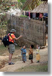asia, backpack, cameras, childrens, clothes, hats, hmong, laos, people, photographers, talking, toddlers, tourists, vertical, villages, photograph