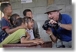 asia, asian, cameras, childrens, clothes, emotions, groups, hats, horizontal, laos, laugh, men, people, river village, showing, smiles, tourists, villages, photograph