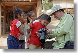 asia, asian, cameras, childrens, clothes, emotions, groups, hats, horizontal, laos, men, people, river village, showing, smiles, tourists, villages, photograph
