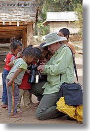 asia, asian, cameras, childrens, clothes, emotions, groups, hats, laos, men, people, river village, showing, smiles, tourists, vertical, villages, photograph