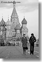 asia, black and white, buildings, churches, couples, landmarks, moscow, near, onion dome, pedestrians, people, pokrovskiy, religious, russia, st basil, st basil cathedral, st. basil, structures, vertical, walking, photograph