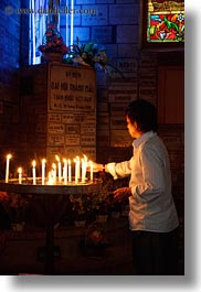 asia, asian, candles, catholic, glow, lights, men, neon, people, saigon, vertical, vietnam, photograph