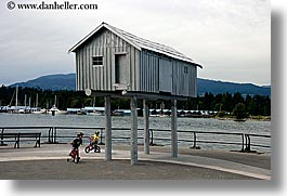 bicycles, bikes, boys, canada, childrens, horizontal, houses, people, stilts, vancouver, photograph