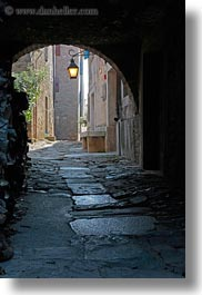 arches, archways, cobblestones, croatia, europe, groznjan, materials, narrow streets, roads, stones, streets, structures, vertical, photograph
