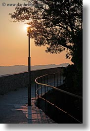 behind, cobblestones, croatia, dusk, europe, glow, lamp posts, lights, materials, motovun, nature, scenics, silhouettes, sky, stones, sun, sunsets, trees, vertical, photograph