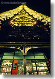 buildings, eiffel tower, europe, france, gifts, glow, glowing, lights, paris, perspective, shops, structures, towers, upview, vertical, photograph