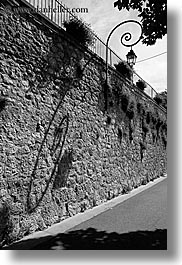 black and white, europe, france, lamps, materials, moustiers, provence, shadows, st marie, stones, streets, vertical, photograph