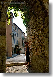 arches, archways, clothes, cobblestones, covered, europe, france, hats, ivy, looking, materials, nature, people, plants, provence, seillans, stones, structures, vertical, womens, photograph
