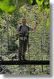 bridge, cameras, clothes, colors, europe, forests, france, green, groups, hats, helanie howard greene, howard, men, nature, people, plants, provence, structures, swing bridge, trees, vertical, photograph