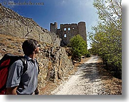 activities, architectural ruins, backpack, buildings, castles, clothes, colors, europe, fortress, france, groups, hiking, horizontal, men, nicos, people, provence, red, structures, sunglasses, viewing, photograph