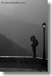 amorgos, black and white, europe, greece, lamp posts, mountains, people, photographers, vertical, photograph