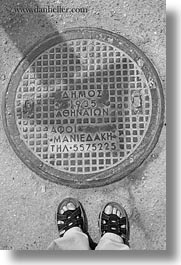 athens, black and white, covers, europe, feet, greece, manholes, streets, vertical, photograph