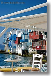 buildings, chairs, europe, flowers, greece, mykonos, tables, vertical, waterfront, photograph