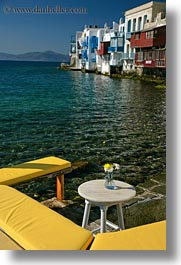 benches, buildings, europe, facing, flowers, greece, mykonos, vertical, water, yellow, photograph