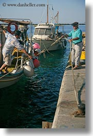 boats, docking, europe, greece, harbor, men, ropes, tinos, vertical, photograph