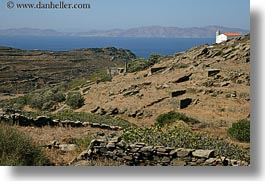 europe, fences, greece, horizontal, houses, mountains, ocean, scenics, stones, tinos, photograph