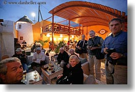 cafes, clothes, dusk, europe, glasses, greece, groups, horizontal, men, people, tourists, photograph