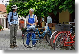 bicycles, brunette, clothes, emotions, europe, groups, hair, hats, horizontal, hungary, lori, men, old, people, smiles, talking, womens, photograph