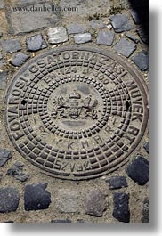 budapest, cobblestones, covers, europe, hungary, irons, manhole covers, manholes, materials, vertical, photograph