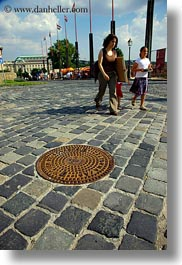 budapest, cobblestones, covers, europe, hungary, irons, manhole covers, manholes, materials, pedestrians, people, vertical, womens, photograph