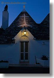 alberobello, buildings, dusk, europe, italy, lamps, puglia, structures, trullis, vertical, photograph