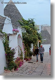 alberobello, buildings, couples, europe, flowers, italy, people, puglia, structures, trullis, vertical, photograph