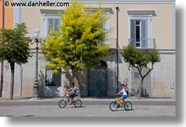 bikes, boys, buildings, europe, green, horizontal, italy, people, puglia, trani, trees, white, photograph