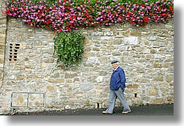 europe, flowers, horizontal, italy, men, montalcino, stones, towns, tuscany, walk, walls, photograph