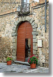 archways, doors, europe, flowers, geraniums, italy, montalcino, stones, towns, tuscany, vertical, woods, photograph