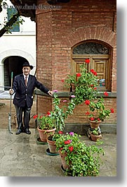 bricks, europe, flowers, gardeners, gardens, geraniums, italy, men, montalcino, shed, towns, tuscany, vertical, photograph