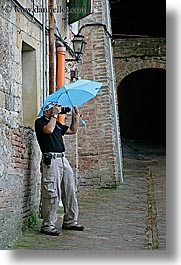 cobblestones, europe, italy, men, people, photographers, siena, tourists, towns, tuscany, umbrellas, vertical, photograph
