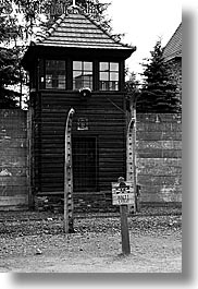 arts, auschwitz, barbed wire, black and white, buildings, design, europe, fences, guard tower, halt, poland, prison, prison camp, signs, structures, towers, vertical, photograph