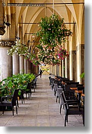 archways, buildings, chairs, europe, flowers, halls, krakow, poland, structures, vertical, photograph