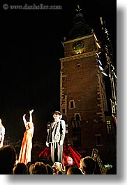 actors, bell towers, bowing, buildings, clock tower, crowds, europe, krakow, nite, people, performance, poland, structures, vertical, photograph