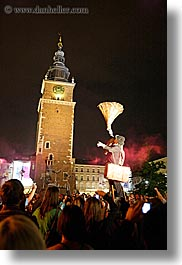 bell towers, buildings, clock tower, cones, crowds, europe, krakow, men, nite, people, performance, poland, structures, vertical, photograph