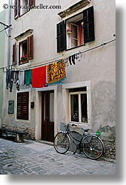 bicycles, clothes, cobblestones, europe, hangings, laundry, pirano, slovenia, vertical, windows, photograph