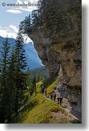 cliffs, clouds, europe, hikers, hiking, kandersteg, lake oeschinensee, nature, people, sky, switzerland, under, vertical, photograph