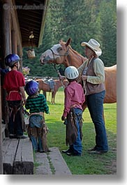 america, childrens, clothes, cowboy hat, hats, helmets, horses, idaho, looking, north america, people, red horse mountain ranch, stables, united states, vertical, photograph
